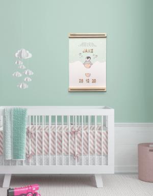 Voorbeeld babykamer met boven het bedje een geboorteposter met pinguïn erop