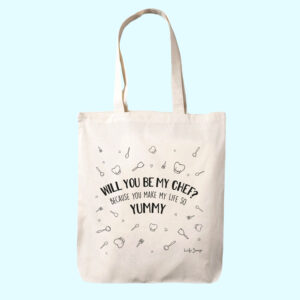 Valentijn teksten op katoenen tas, er staat 'Will you be my chef? Because you make my day so yummy' met daarom heen geillustreerde koksmutsen, spatels en lepels.